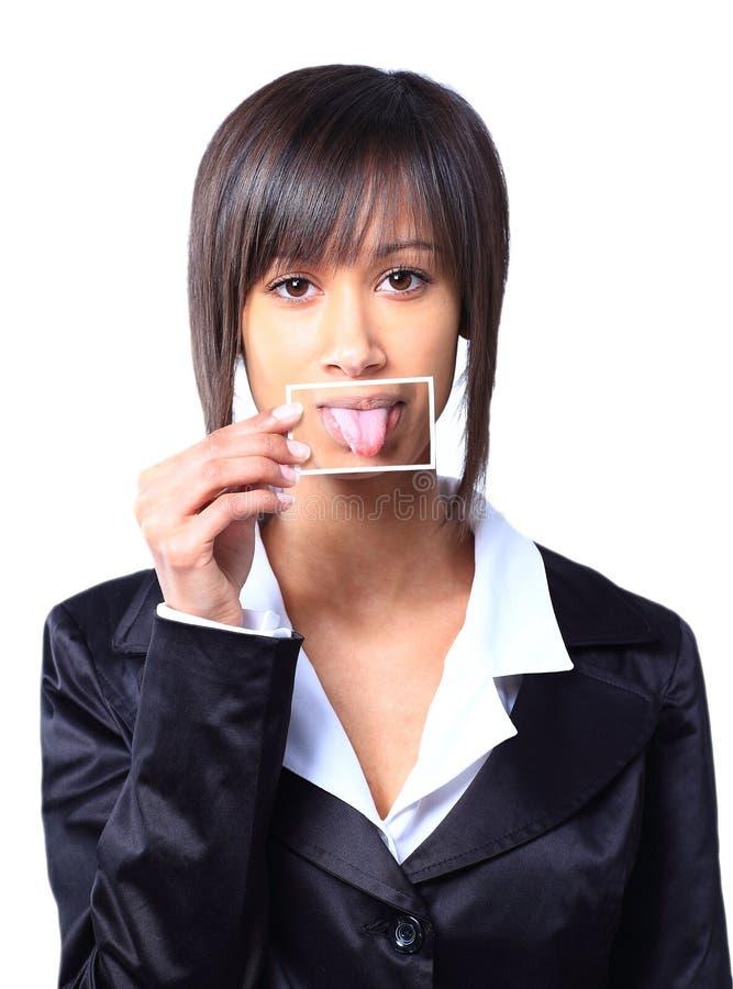 Muchacha que sostiene una tarjeta con la foto su lengua fotografía de archivo