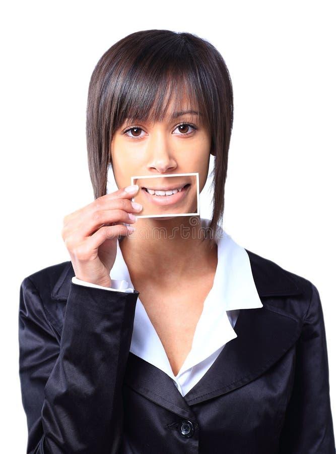 Muchacha que sostiene una tarjeta con la foto su sonrisa imagen de archivo