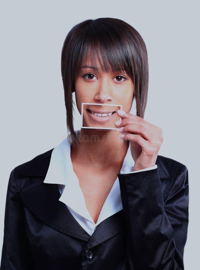 Muchacha que sostiene una tarjeta con la foto su sonrisa delante de su boca imagen de archivo