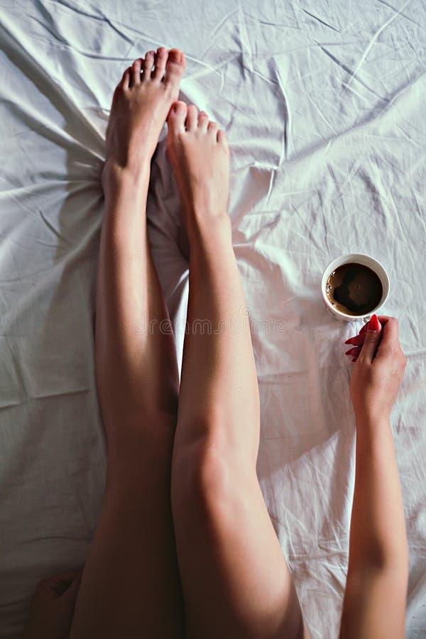 Muchacha que sostiene una taza de café en la cama fotografía de archivo