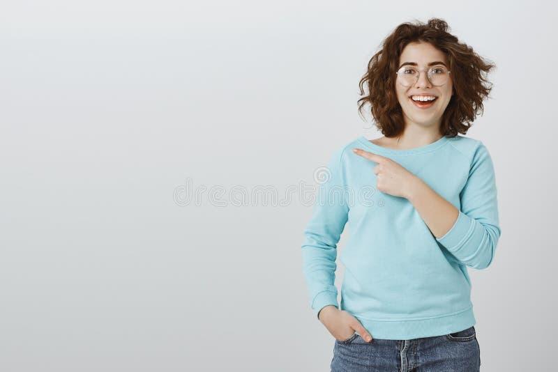 Muchacha que sugiere para preguntar a compañero de trabajo acerca del detalle Estudiante alegre positivo con corte de pelo rizado fotos de archivo libres de regalías