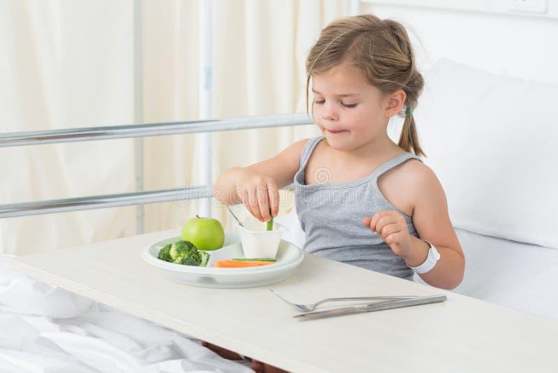 Muchacha que tiene comida sana en hospital imagenes de archivo