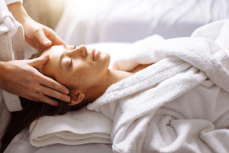 Muchacha que tiene masaje facial del balneario en salón de belleza lujoso imagen de archivo libre de regalías