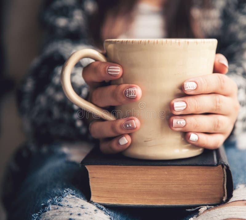 Muchacha que tiene una rotura con la taza de café fresco después de libros o de estudiar de lectura fotos de archivo libres de regalías