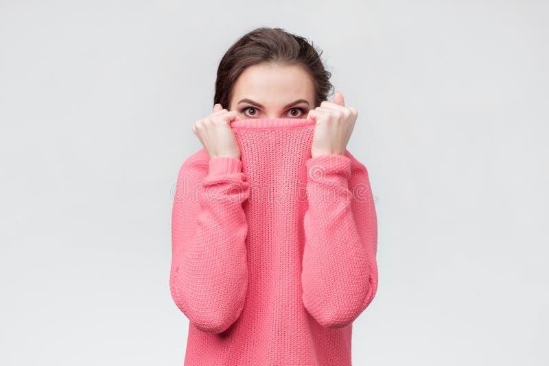 Muchacha que tira de su hdidng de arriba del suéter de moda de problemas fotos de archivo libres de regalías