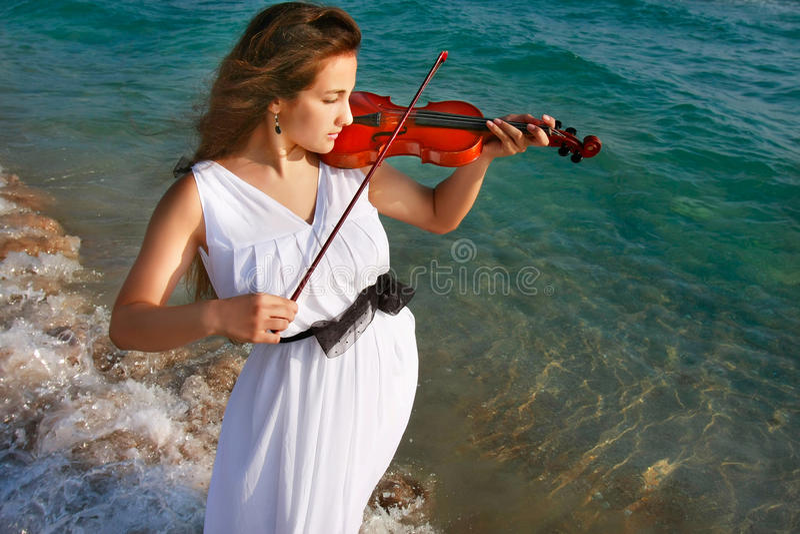 Muchacha que toca el violín en fondo del mar fotografía de archivo
