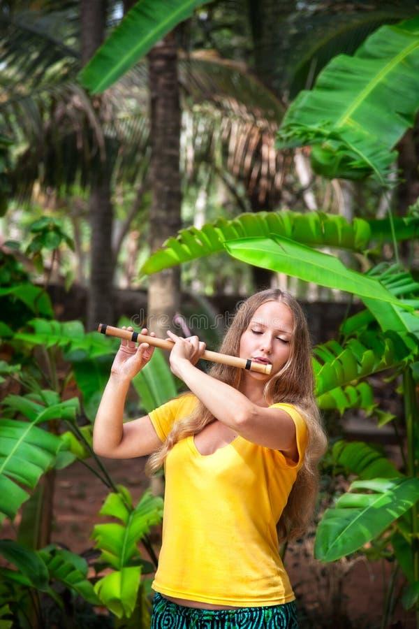 Muchacha que toca la flauta de bambú fotos de archivo