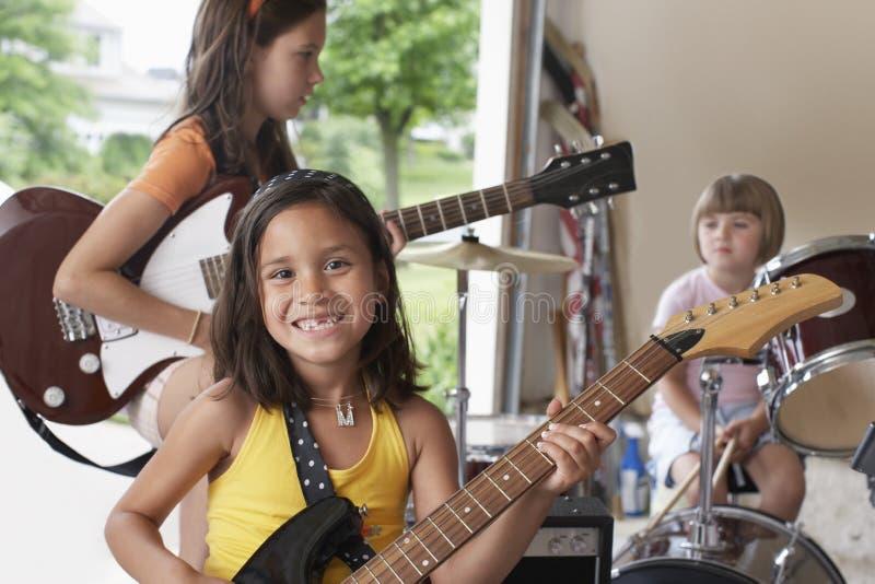 Muchacha que toca la guitarra con la banda en garaje imagen de archivo
