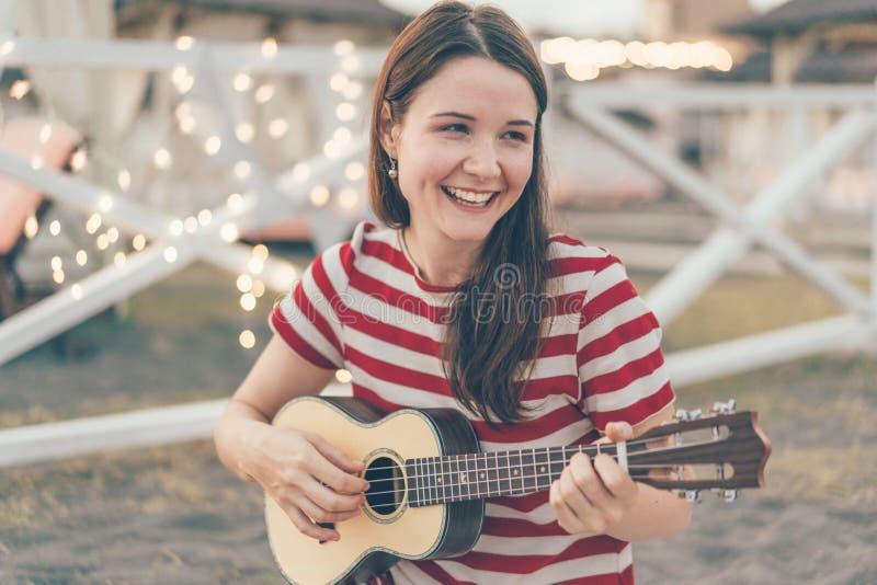 Muchacha que toca la guitarra del ukelele fotografía de archivo
