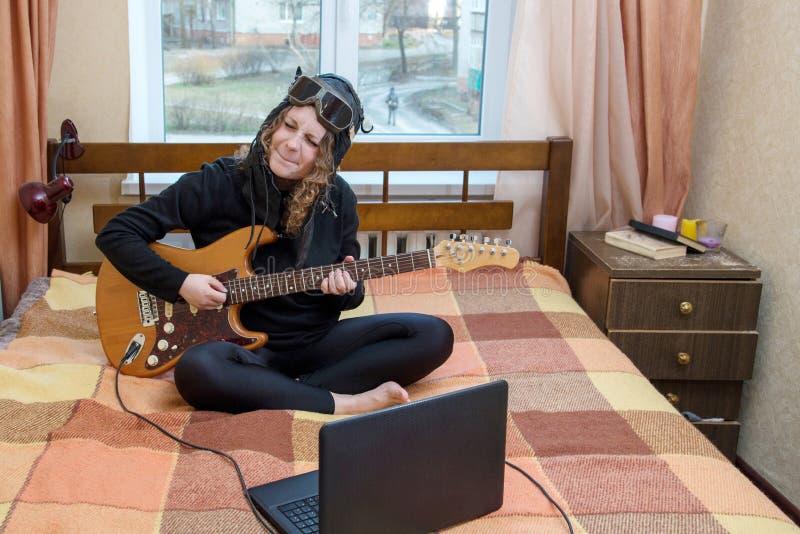 Muchacha que toca la guitarra eléctrica que se sienta en la cama fotografía de archivo