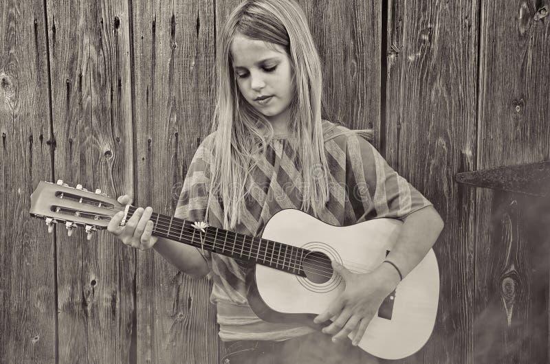 Muchacha que toca la guitarra por el granero en niebla fotografía de archivo