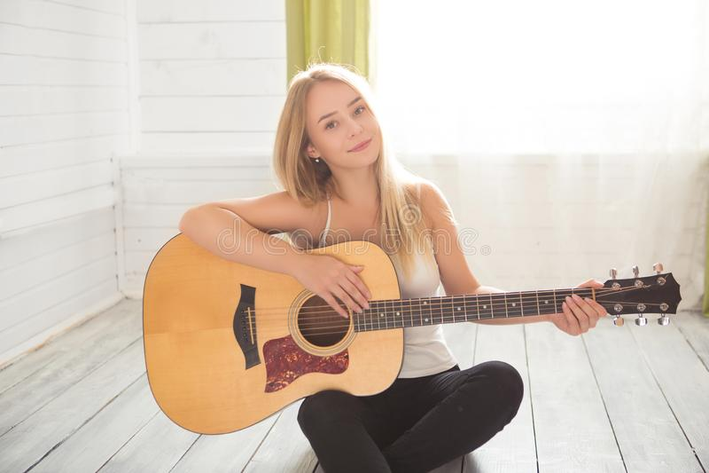 Muchacha que toca la guitarra y que canta Mujer joven con el pelo largo que estudia música en casa Mujer que se sienta en guit ac foto de archivo