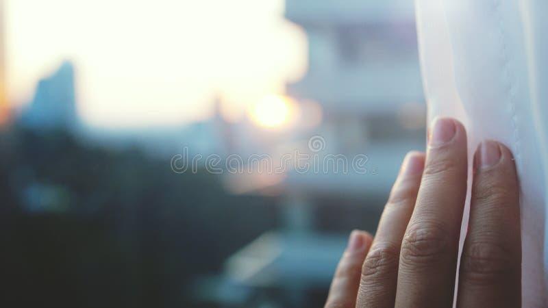 Muchacha que toca la luz del sol a mano en su sitio en casa La mano femenina abre las cortinas fotos de archivo libres de regalías