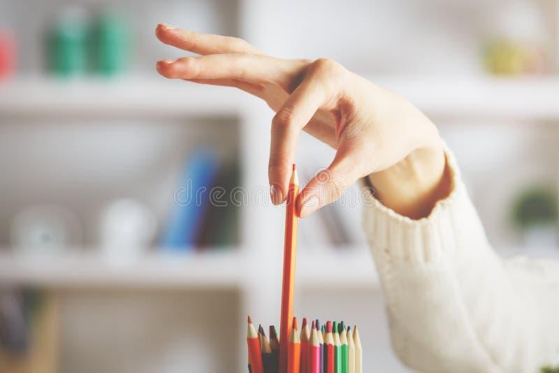 Muchacha que toma el lápiz rojo foto de archivo
