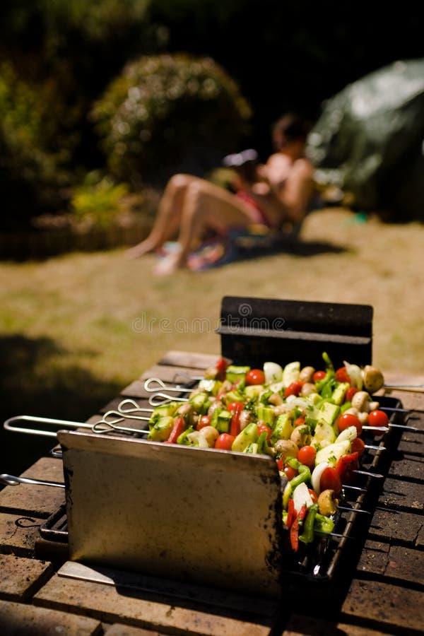 Muchacha que toma el sol del Shish-kebab vegetal de la barbacoa fotos de archivo libres de regalías