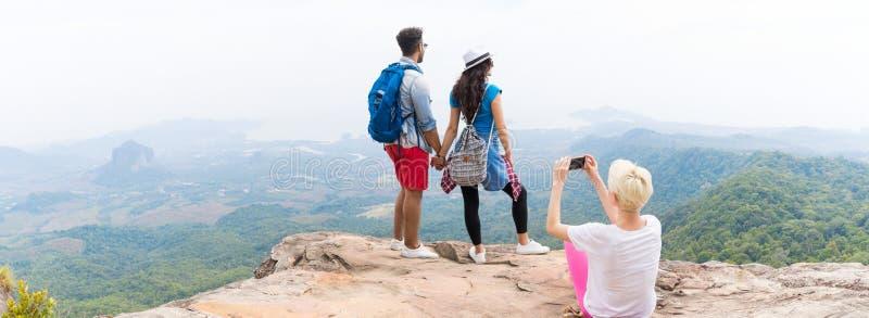 Muchacha que toma la foto de pares con las mochilas que presentan sobre paisaje de la montaña en panorama elegante del teléfono d imagen de archivo libre de regalías