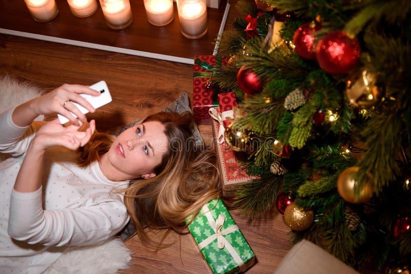 Muchacha que toma un selfie del Año Nuevo en un área adornada imagenes de archivo