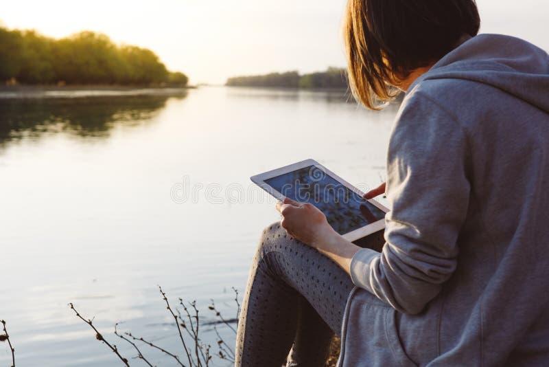 Muchacha que trabaja con la tableta en el río foto de archivo