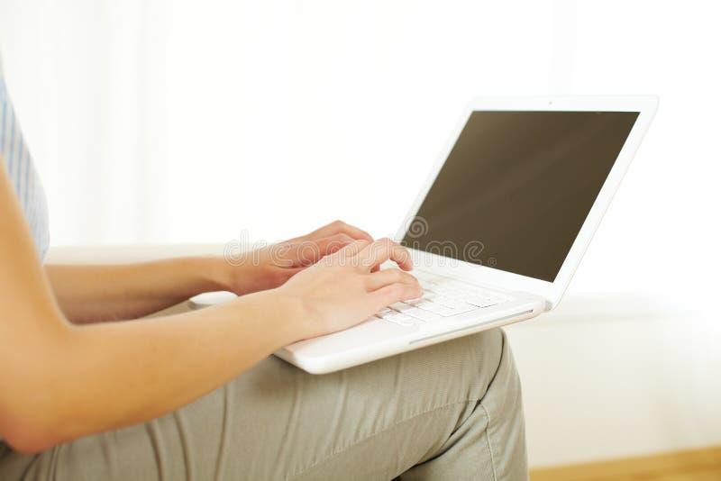 Muchacha que trabaja con una computadora portátil foto de archivo
