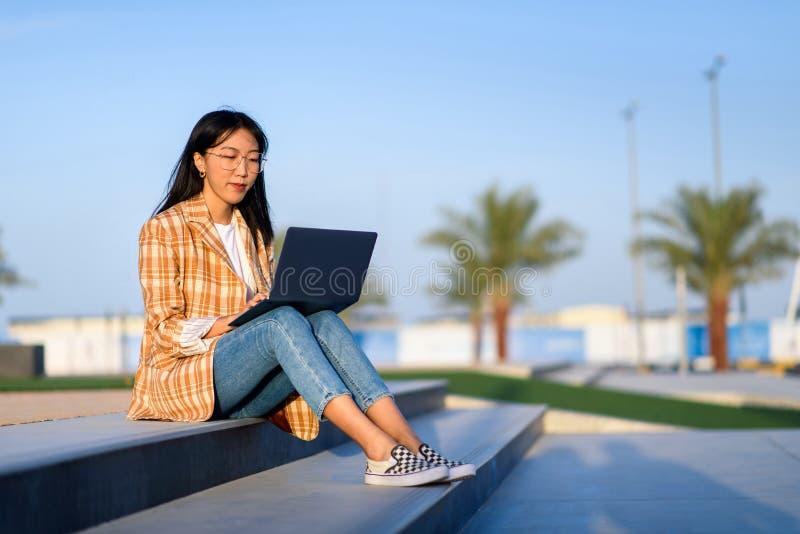 Muchacha que trabaja en el ordenador portátil al aire libre fotografía de archivo