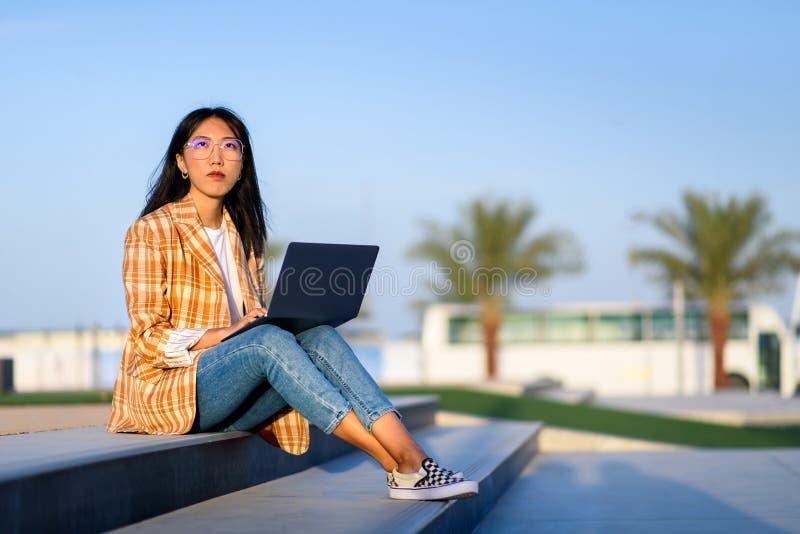 Muchacha que trabaja en el ordenador portátil al aire libre foto de archivo