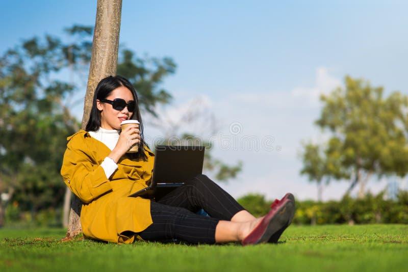 Muchacha que trabaja en el ordenador portátil en el parque foto de archivo libre de regalías