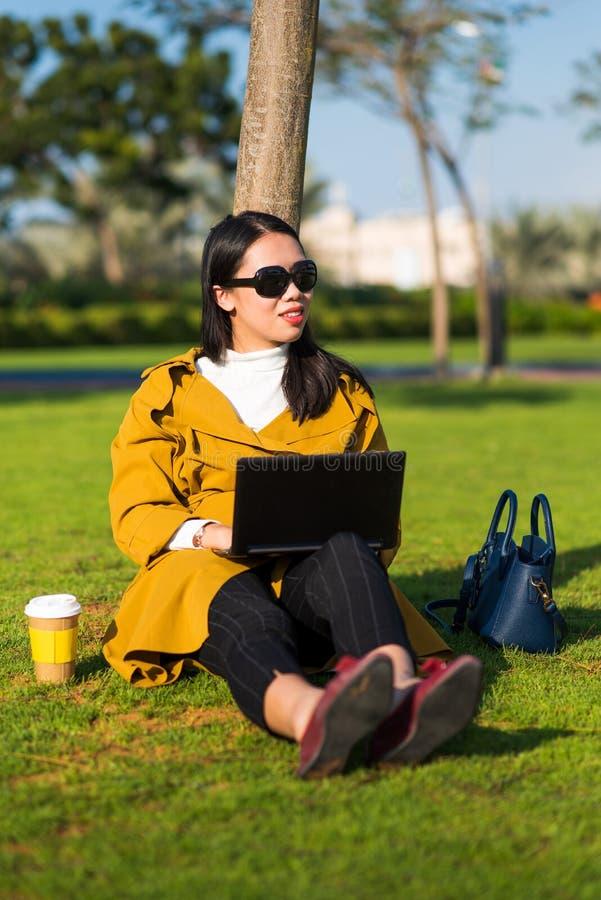 Muchacha que trabaja en el ordenador portátil en el parque imagen de archivo