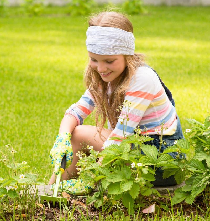 Muchacha que trabaja en las plantas de la preparación del jardín fotos de archivo
