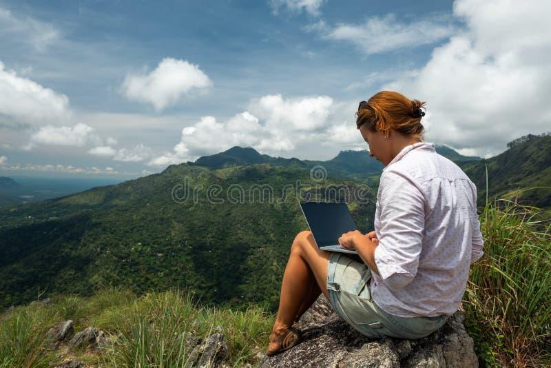 Muchacha que trabaja en su ordenador en el top de la montaña fotos de archivo