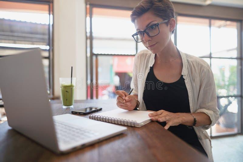 Muchacha que trabaja en un café Concepto independiente imagen de archivo