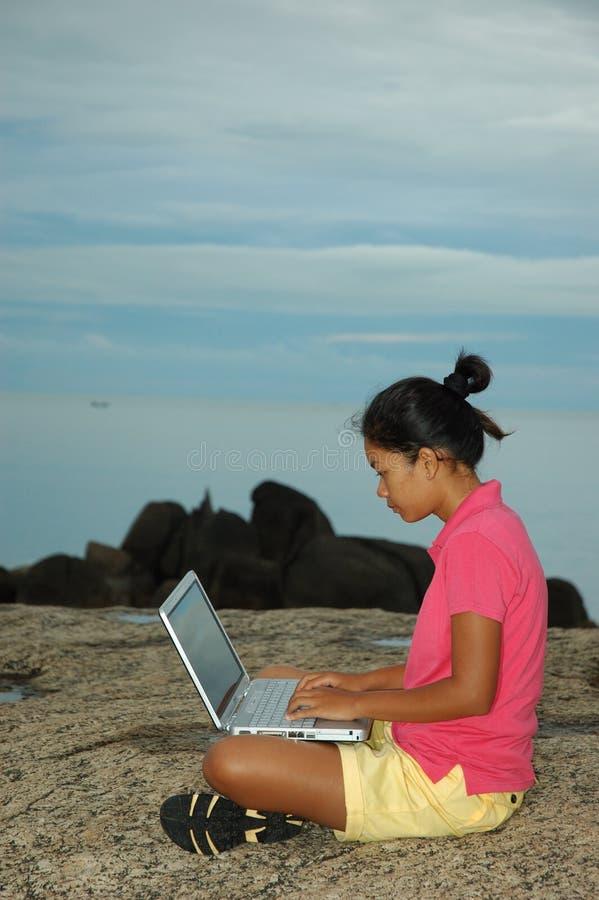 Muchacha que usa el cuaderno afuera en rocas foto de archivo