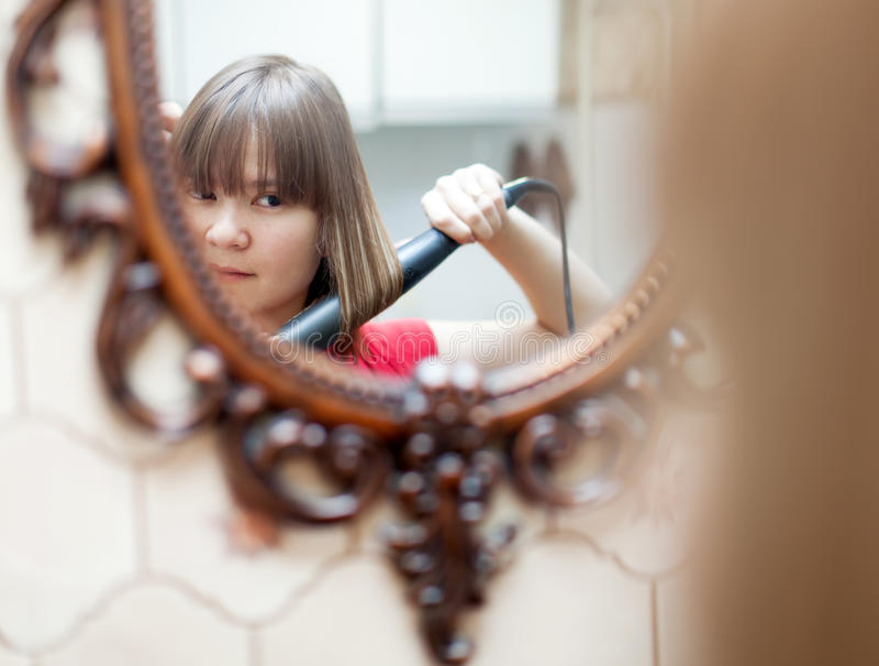 Muchacha que usa el hierro que se encrespa antes de espejo imágenes de archivo libres de regalías