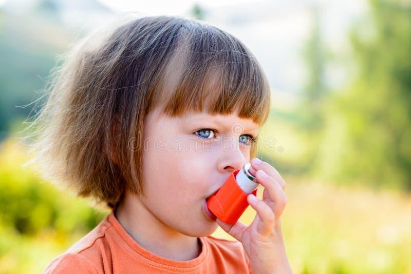Muchacha que usa el inhalador del asma imagenes de archivo