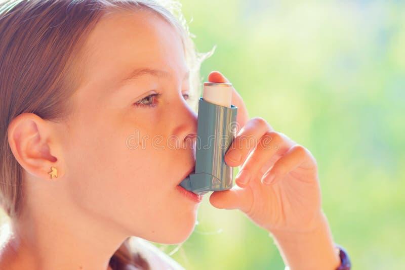 Muchacha que usa el inhalador del asma en un parque fotos de archivo