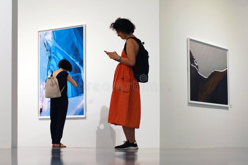Muchacha que usa el mensajero o la red social en su teléfono móvil en museo foto de archivo libre de regalías