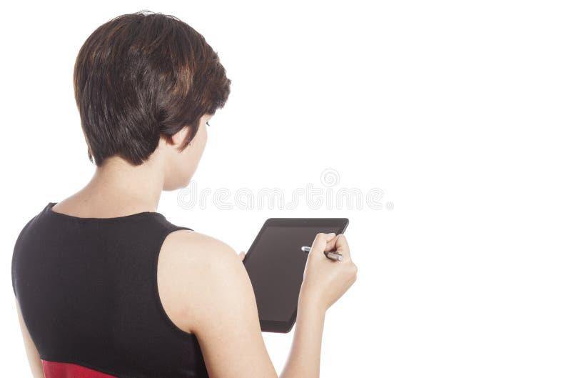 Muchacha que usa el ordenador de la tablilla fotografía de archivo