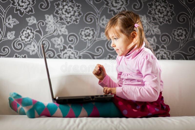 Muchacha que usa el ordenador portátil fotografía de archivo
