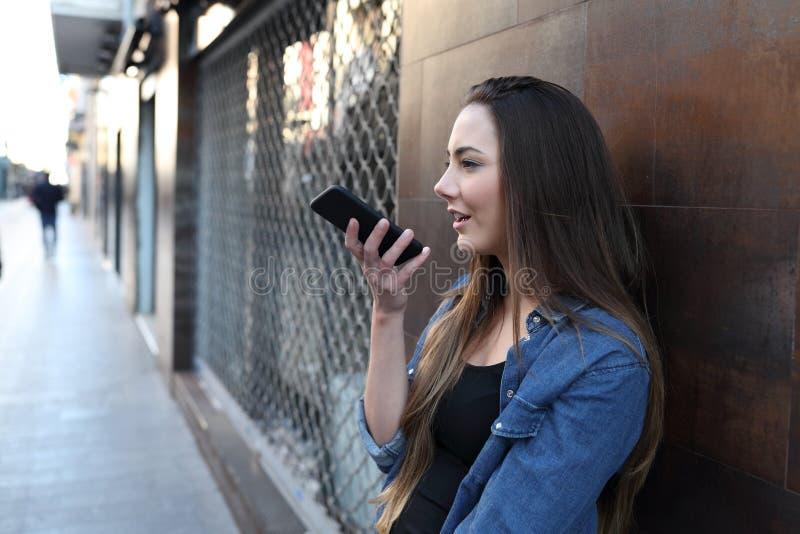 Muchacha que usa el reconocimiento vocal en el teléfono elegante afuera fotos de archivo libres de regalías
