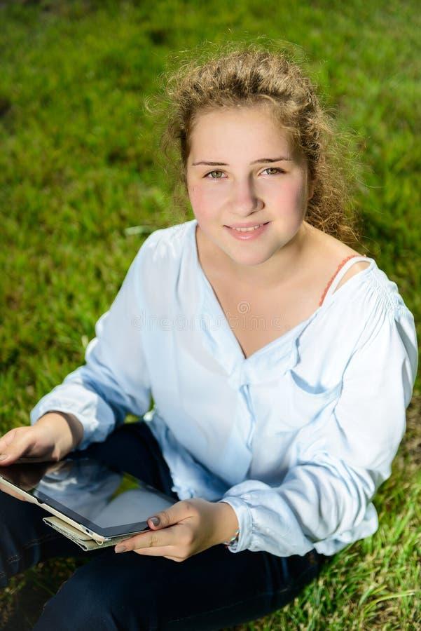 Muchacha que usa la PC de la tableta y sentándose en la hierba verde foto de archivo libre de regalías