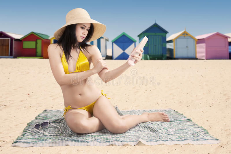 Muchacha que usa la protección solar con el fondo de la playa imágenes de archivo libres de regalías
