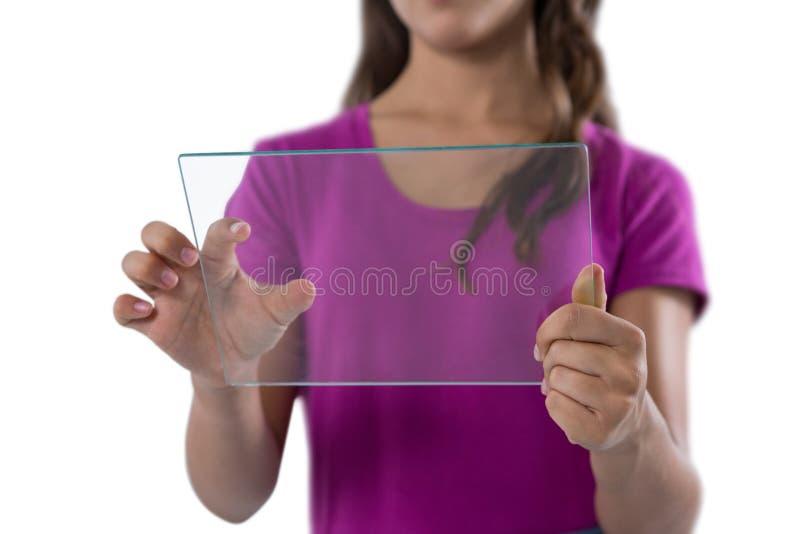 Muchacha que usa la tableta digital de cristal contra el fondo blanco foto de archivo libre de regalías