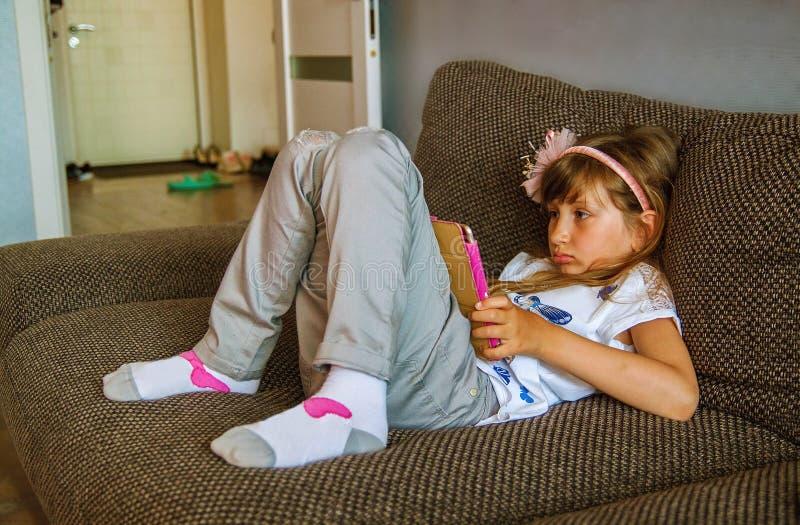 Muchacha que usa la tableta digital en el sofá en casa imagenes de archivo