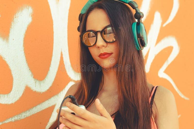 Muchacha que usa su dispositivo móvil para escuchar música imagen de archivo