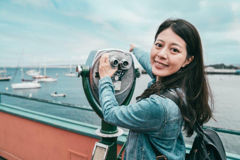 Muchacha que usa un telescopio y mirando a la cámara foto de archivo libre de regalías