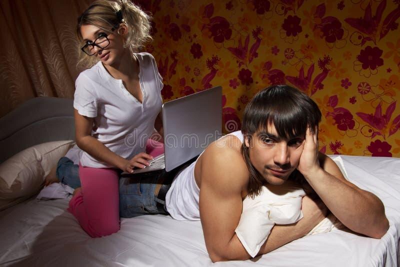 Muchacha que usa una computadora portátil en su parte posterior del `s del novio