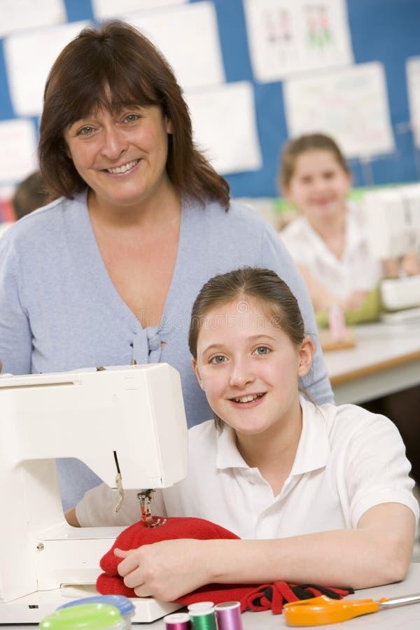 Muchacha que usa una máquina de coser imagen de archivo