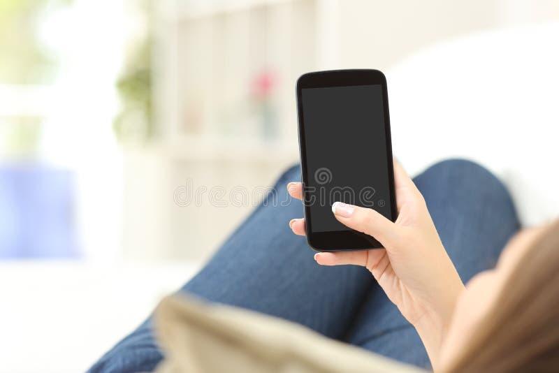 Muchacha que usa y mostrando una pantalla en blanco del teléfono foto de archivo