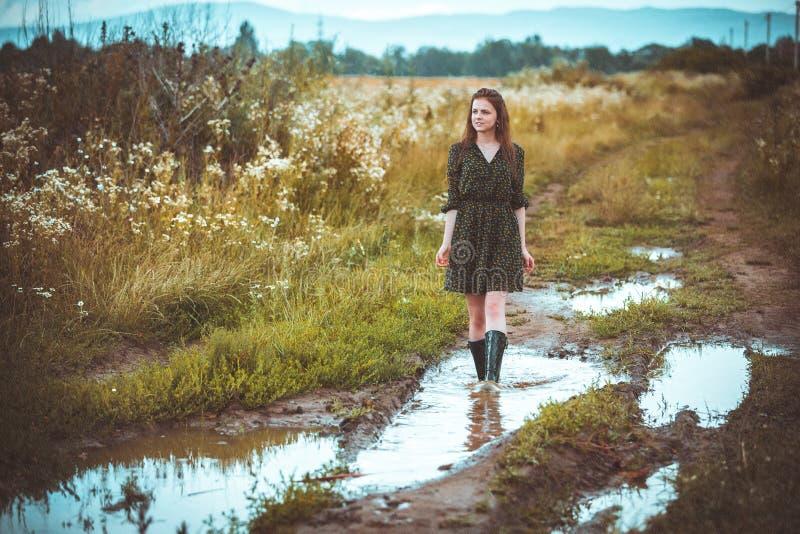 Muchacha que va en el camino rural a tiempo una lluvia fotografía de archivo libre de regalías