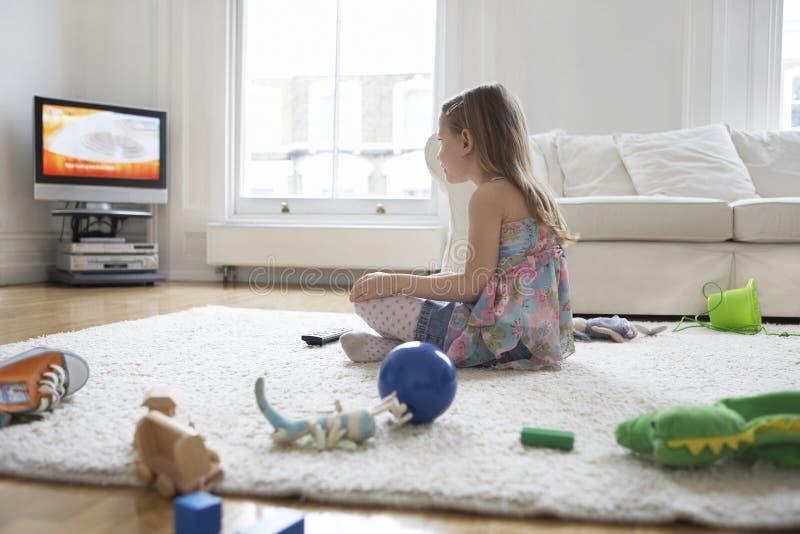 Muchacha que ve la TV con los juguetes en piso imagen de archivo libre de regalías