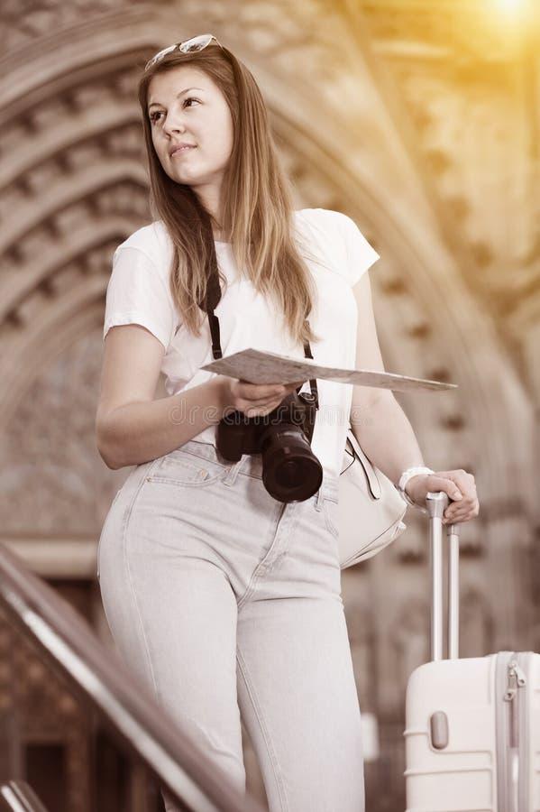 Muchacha que viaja agradable que usa el mapa de papel foto de archivo